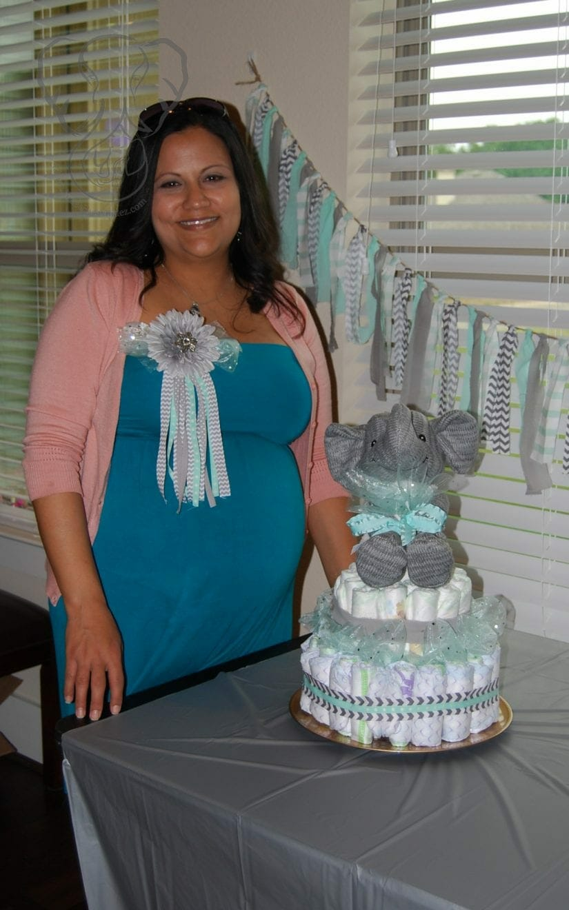 Expecting mother Miranda at her baby shower. Miranda is wearing a blue dress and pink cardigan, with a mom to be badge on her chest. She is smiling at the camera, standing behind a table with a diaper cake on it. On top of the diaper cake is Adrian's elephant, wrapped in teal ribbons. (Friend's photo)