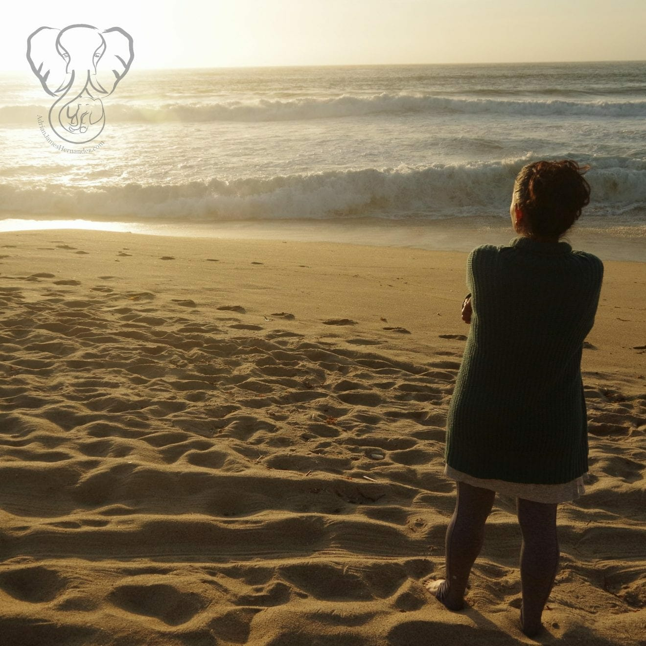 Miranda standing on a deserted beach in California at sunset. She is wrapped in a large sweater and staring off camera (Synch Media)