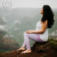 Miranda sitting on the edge of red dirt on the ledge of a cliff in Waimea Canyon, Kaua'i, Hawai'i. Miranda is wearing a white shirt and lavender yoga pants, and is practicing yogic breathing while looking into the distance of the canyon (Luna Kai Photography)