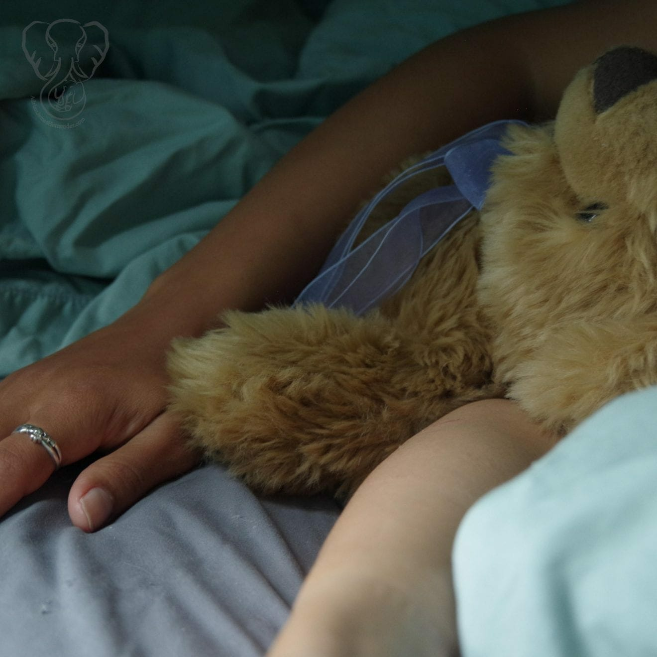Miranda and her Comfort Cub lying in bed in the dark. Miranda's arm is wrapped around the cub, and her clauddagh ring is visible on her right ring finger (Synch Media)