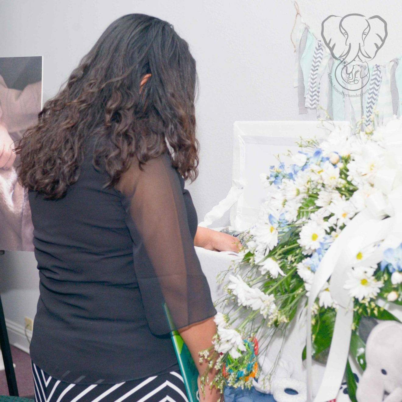 Miranda standing in front of Adrian's casket at his funeral. She is wearing black and facing away from the camera. The casket is white, with a spray of white daisies and bluebonnets on top. Miranda's hand is reaching into the casket to touch her son. (Modern Lux Photography)