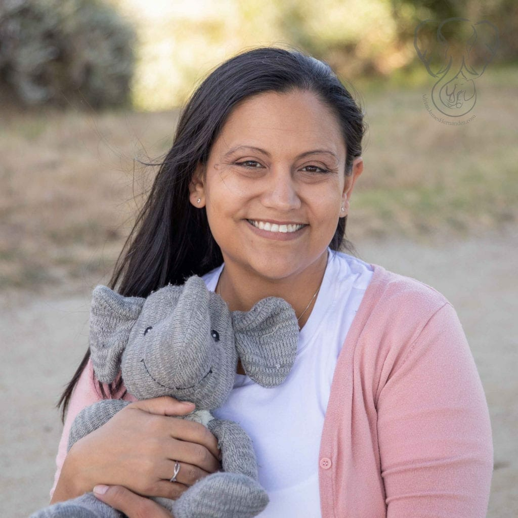 Miranda holding Adrian's elephant in a park in California. It is a sunny afternoon. Miranda is wearing a white shirt and pink cardigan and smiling. (Sarah Perry Photography)