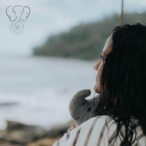 Miranda holding Adrian's Elephant at Nukoli'i Beach Park, Kaua'i, Hawai'i. It is an overcast day and Miranda is facing away from the camera, looking towards the grayish horizon (Luna Kai Photography)