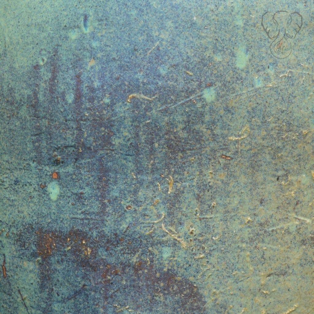Close up of metallic artwork in rustic red blending into blues and greens, found in California (Miranda Hernandez)