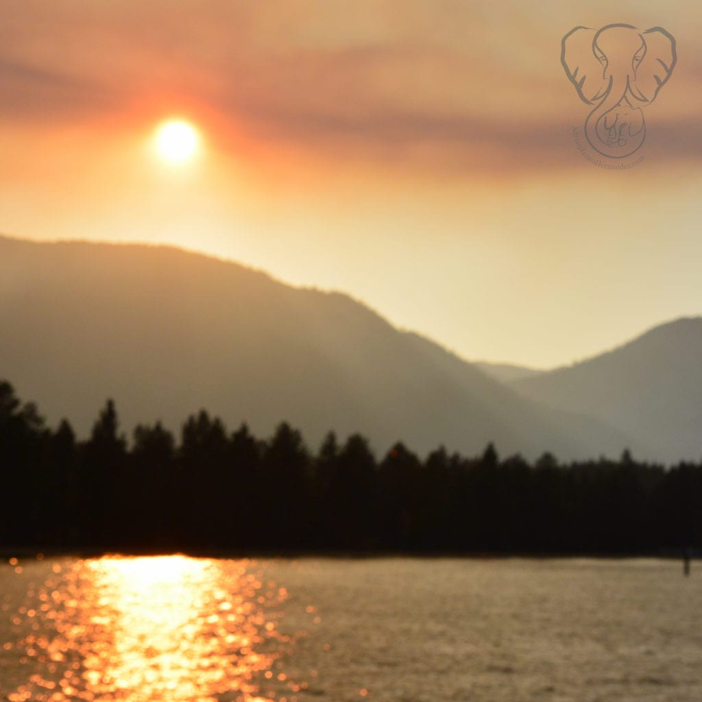 Orangish sunset over North Lake Tahoe, with mountains and trees in the background (Miranda Hernandez)