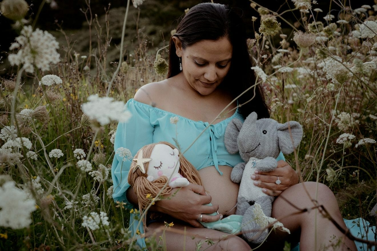 Miranda with Adrian's Elephant and Peanut's Mermaid in a field of wildflowers in New Zealand. Miranda is wearing a light blue maternity gown open at the belly. She is holding the stuffed animals in each arm and looking down at her belly (Two Little Starfish)