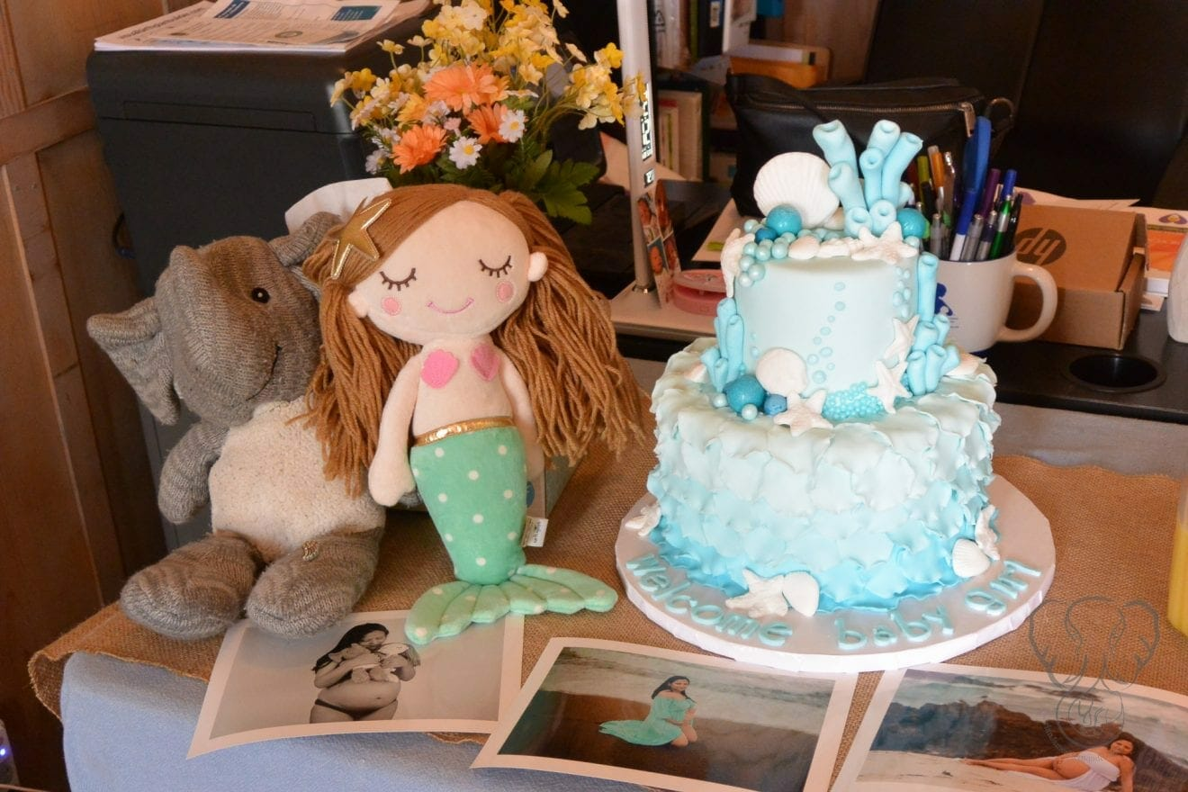 Adrian's Elephant and Peanut's Mermaid sitting next to the ocean-themed cake at Peanut's baby shower. There are 3 maternity photos of Miranda sitting on the table in front of the cake (Miranda Hernandez)
