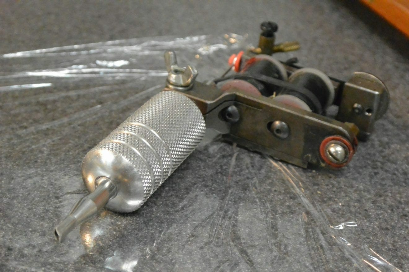 Close up of the tattoo gun, sitting on top of a saran-wrapped table (Miranda Hernandez)