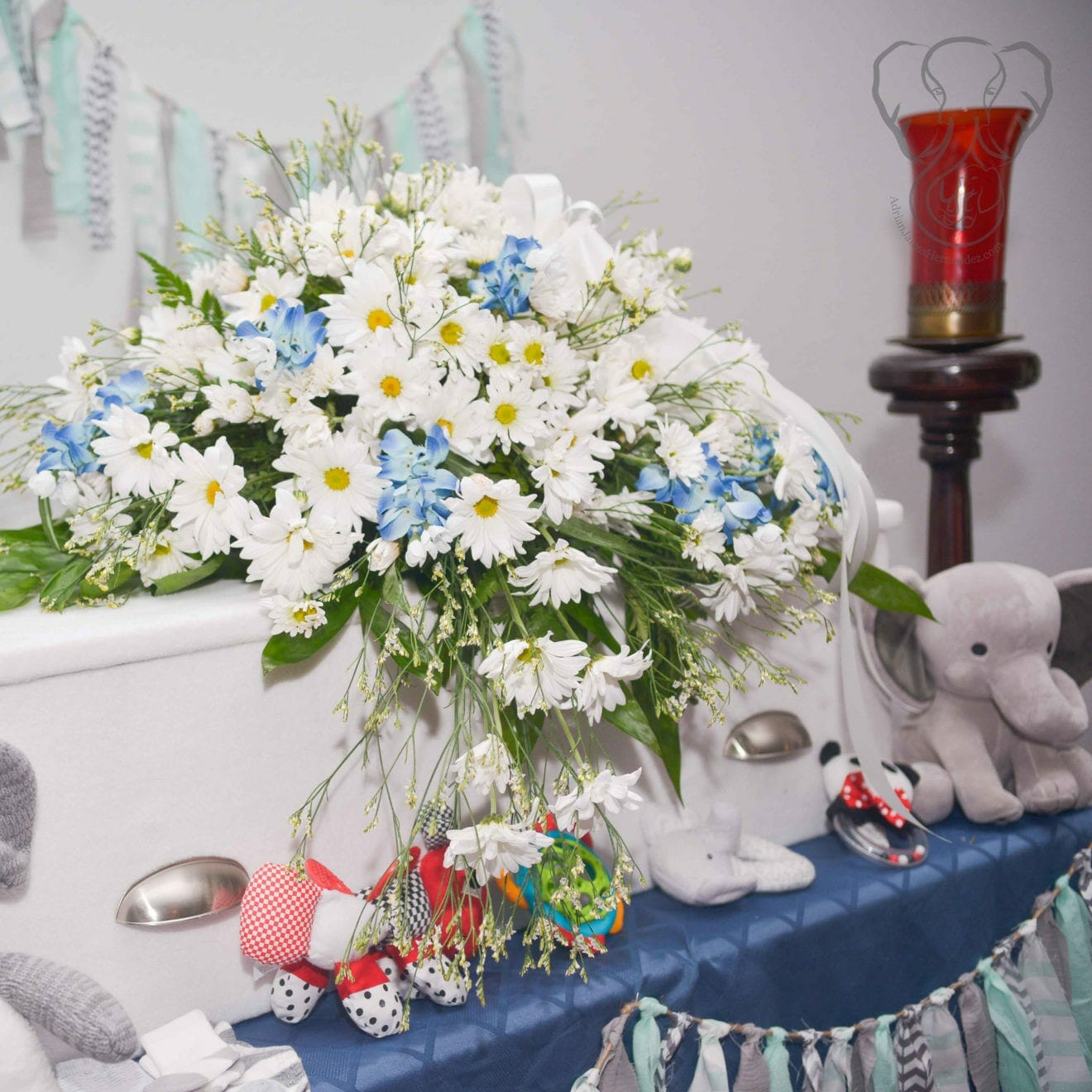 White child's casket covered in arrangement of white daisies and bluebonnets. There are children's toys in front of the casket (Modern Lux Photography)