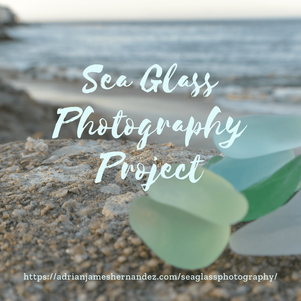 """Close-up of blue and green sea glass sitting on pebbly rock at sunset. The words """"Sea Glass Photography Project"""" are centered in light green text. The address of the Facebook group is written below in white text: https://www.instagram.com/seaglassphotographyproject/"""