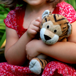 Four-year-old girl sitting outside with her stuffed animal tiger. Image is close-up mainly of tiger in girl's arms (FamilyFotographer, Getty Images)