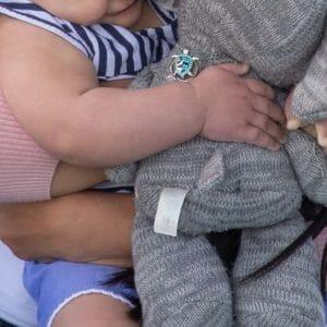 Miranda holding Peanut and Adrian's elephant. Peanut's hand is wrapped around Adrian's elephant.