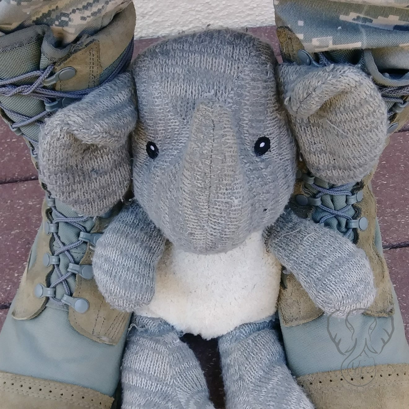 A light gray stuffed elephant nestled between sage-green military boots