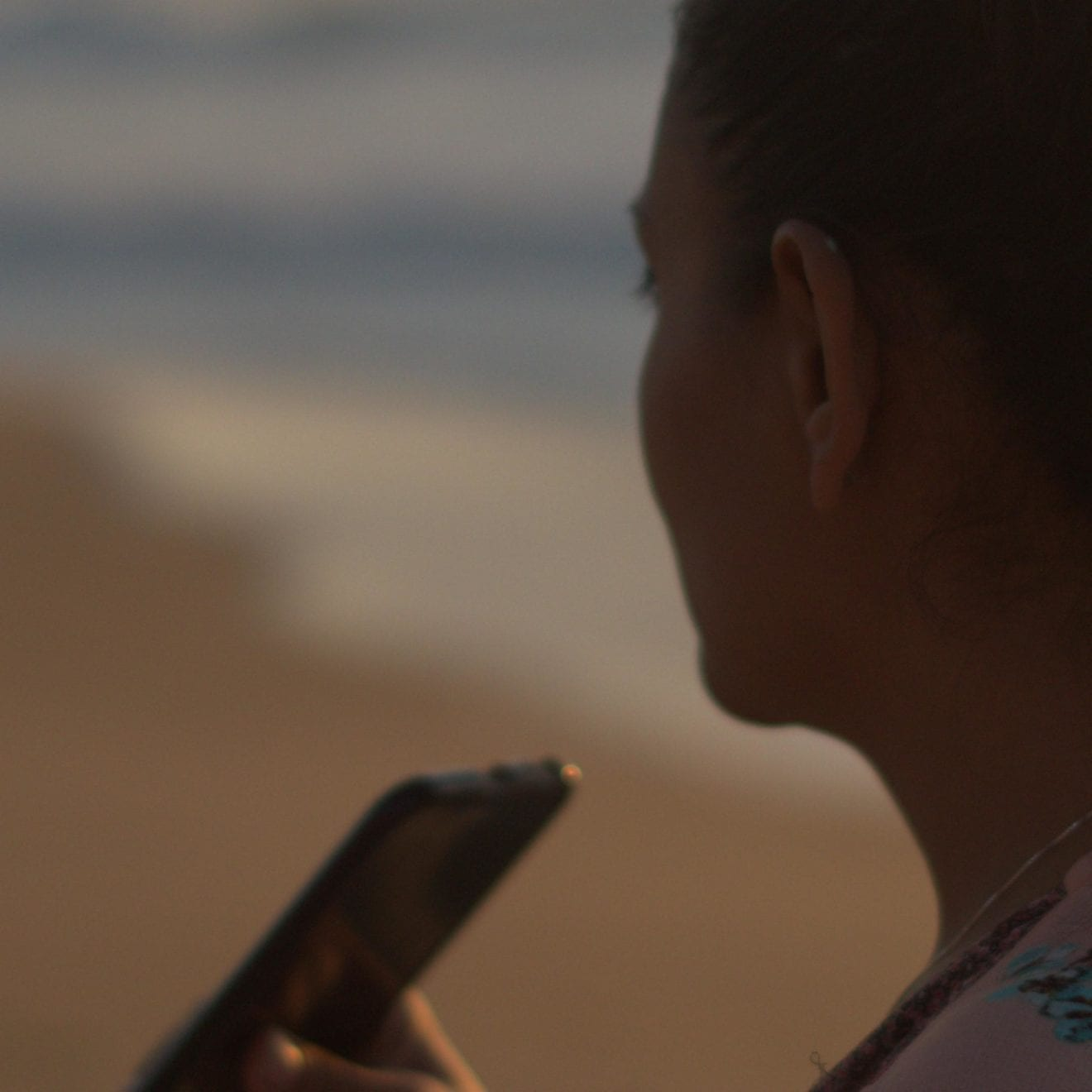 Miranda on the beach in California, speaking into her cell phone at sunset. This is how Miranda writes a lot of her letters to Adrian