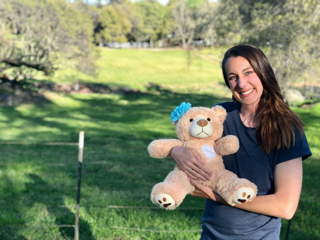 Bethany holding Marlowe's Molly Bear in a shaded area in front of a green field