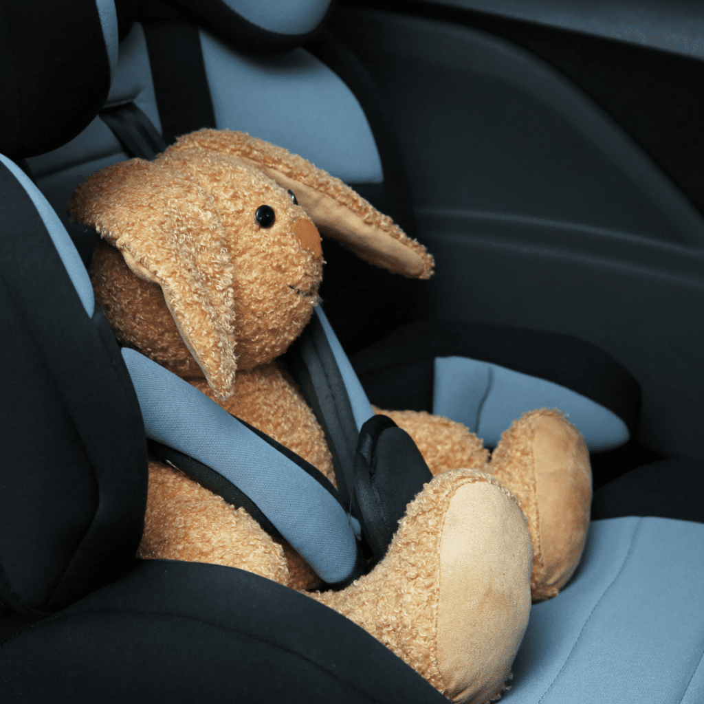 Toy bunny sitting in baby safety seat (Pixelshot)