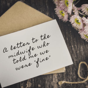 """White letter paper on top on a brown envelope sitting on a dark wooden desk. The letter says, """"A letter to the midwife who told me we were """"fine"""""""" in cursive lettering. There are light pink flowers and a piece of twine to the right of the letter. (Mybona, Getty Images)"""