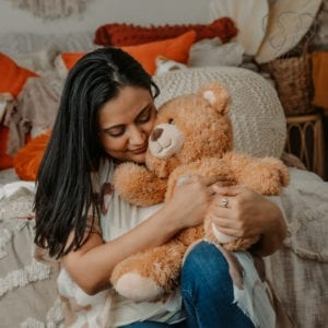 Mother holding a molly bear in a bedroom. The mother is wearing a loose white patterned kimono is snuggling into the bear with eyes closed. The bear is tan, with lighter cream markings. (Liz Morales Photography)