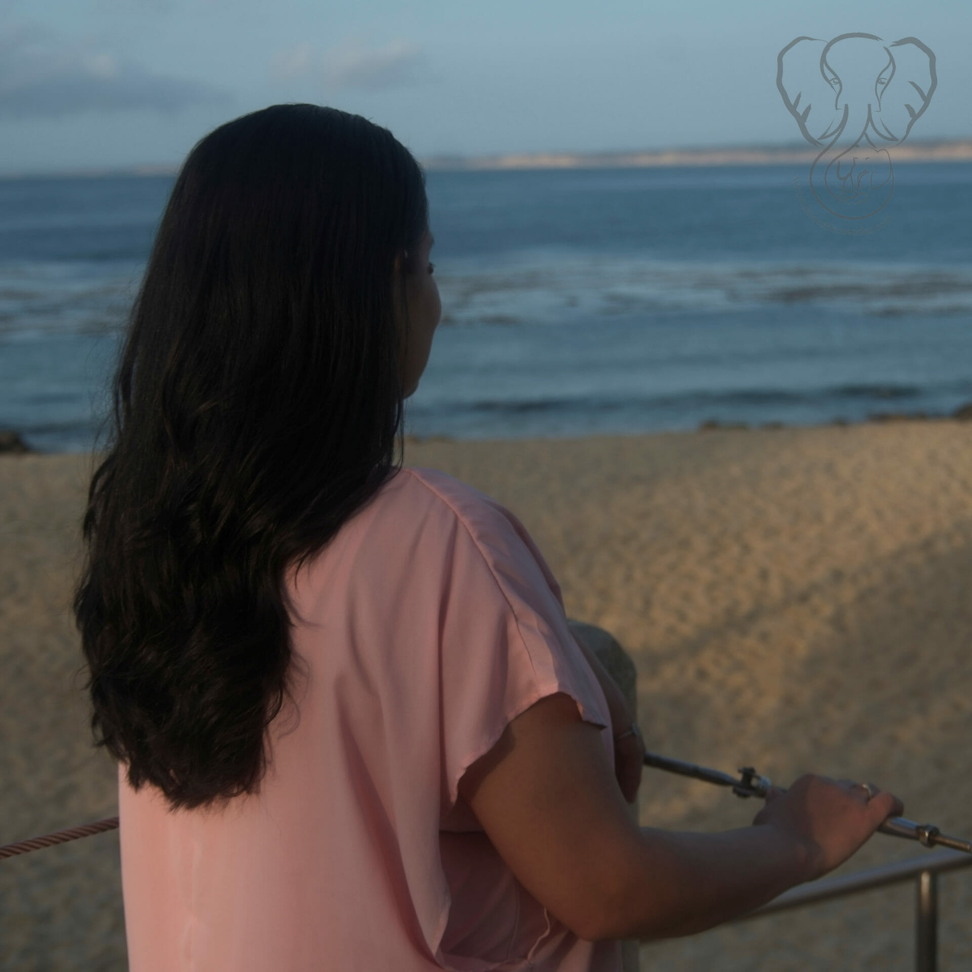 Rear view of Miranda facing the ocean. Miranda is wearing a loose pink shirt and her dark hair is down on her back. (Synch Media)