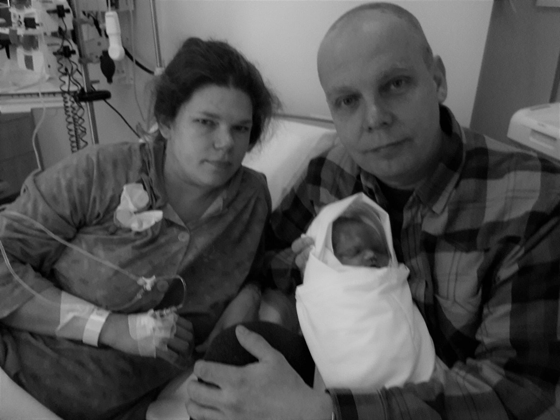 Mother Lotta, Father, and baby Louna in the hospital after birth. Father is holding Louna is his arms, while Lotta sits next to him on the hospital bed. (photo contributed by Lotta)